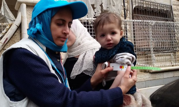 A Unicef worker measures the arm of a malnourished child in Madaya