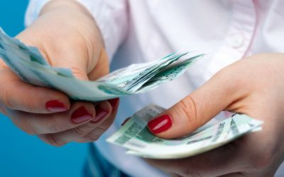 Hands of an unidentified woman with ruble banknotes